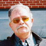 Ren'e Pellerin head and neck photo.  Looking directly at the camera with salt and peper hair, a mustache but clean shaven, and wearing amber colored glasses.